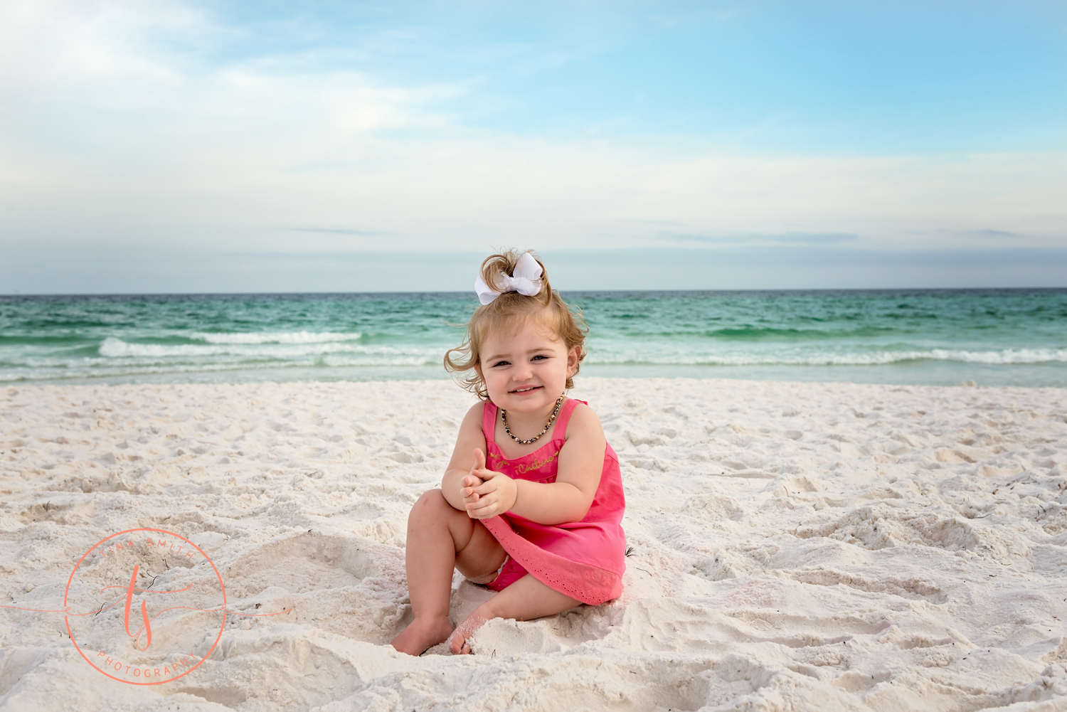 baby girl sitting in beach sand smiling for camera