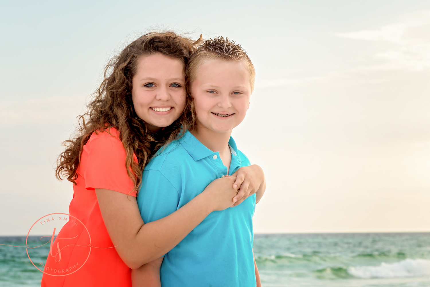 brothers and sister hugging and smiling on the beach for photography