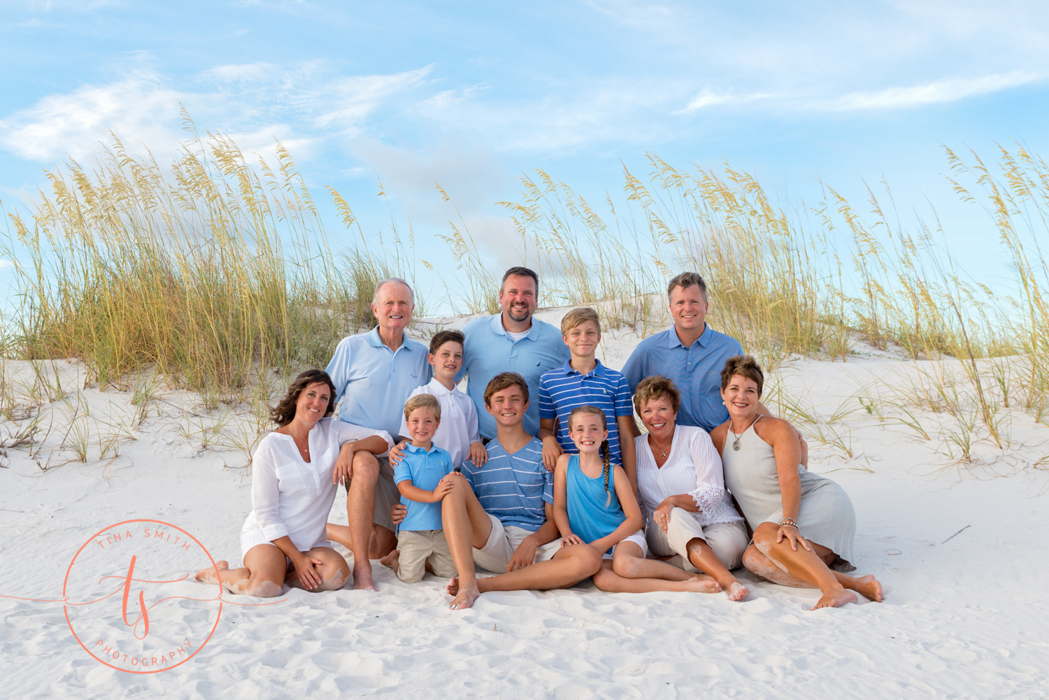 large family sitting on the beach in destin posing for photos