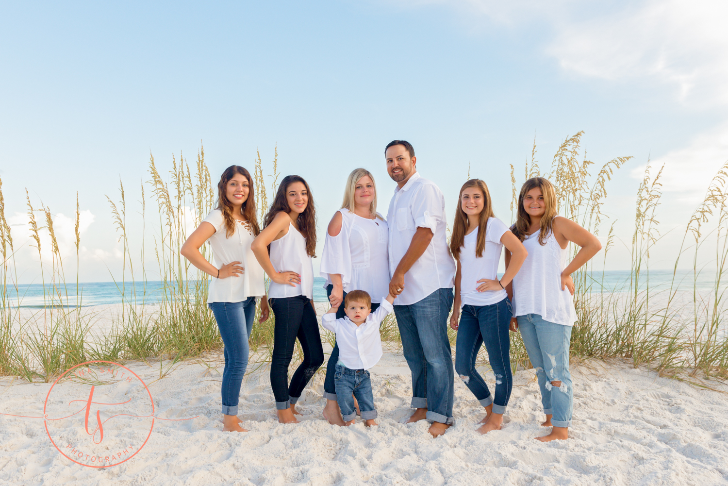 large family dressed in white posing on the beach for destin photographer