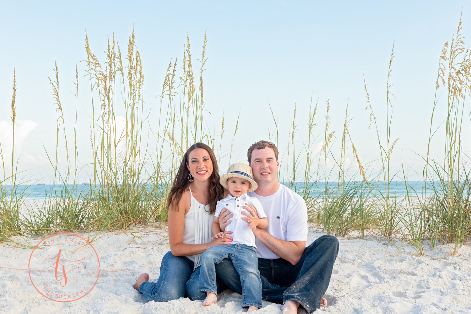 family of three sitting on the beach posing for destin family photographer