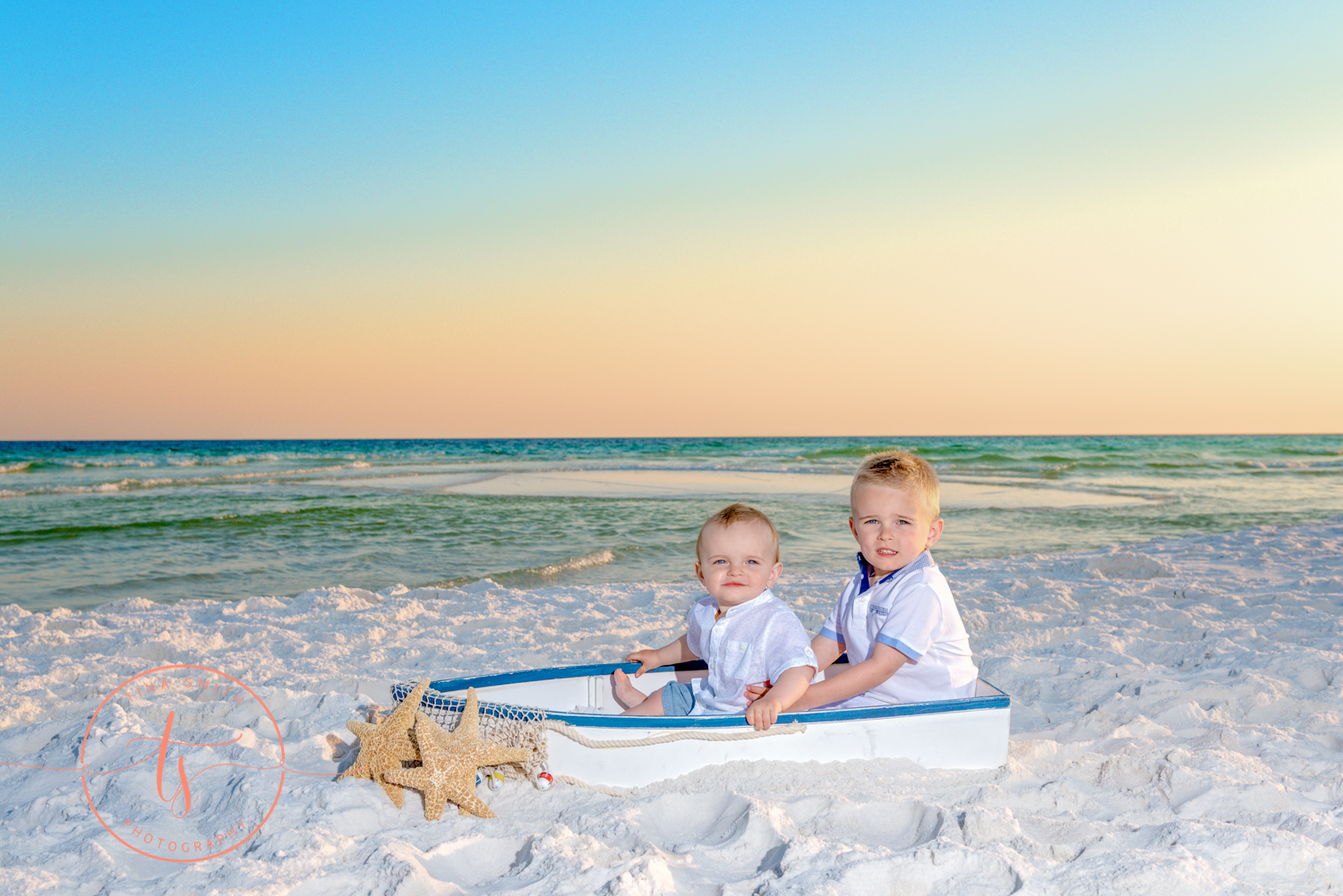 2 brothers sitting on beach in a boat at sunset
