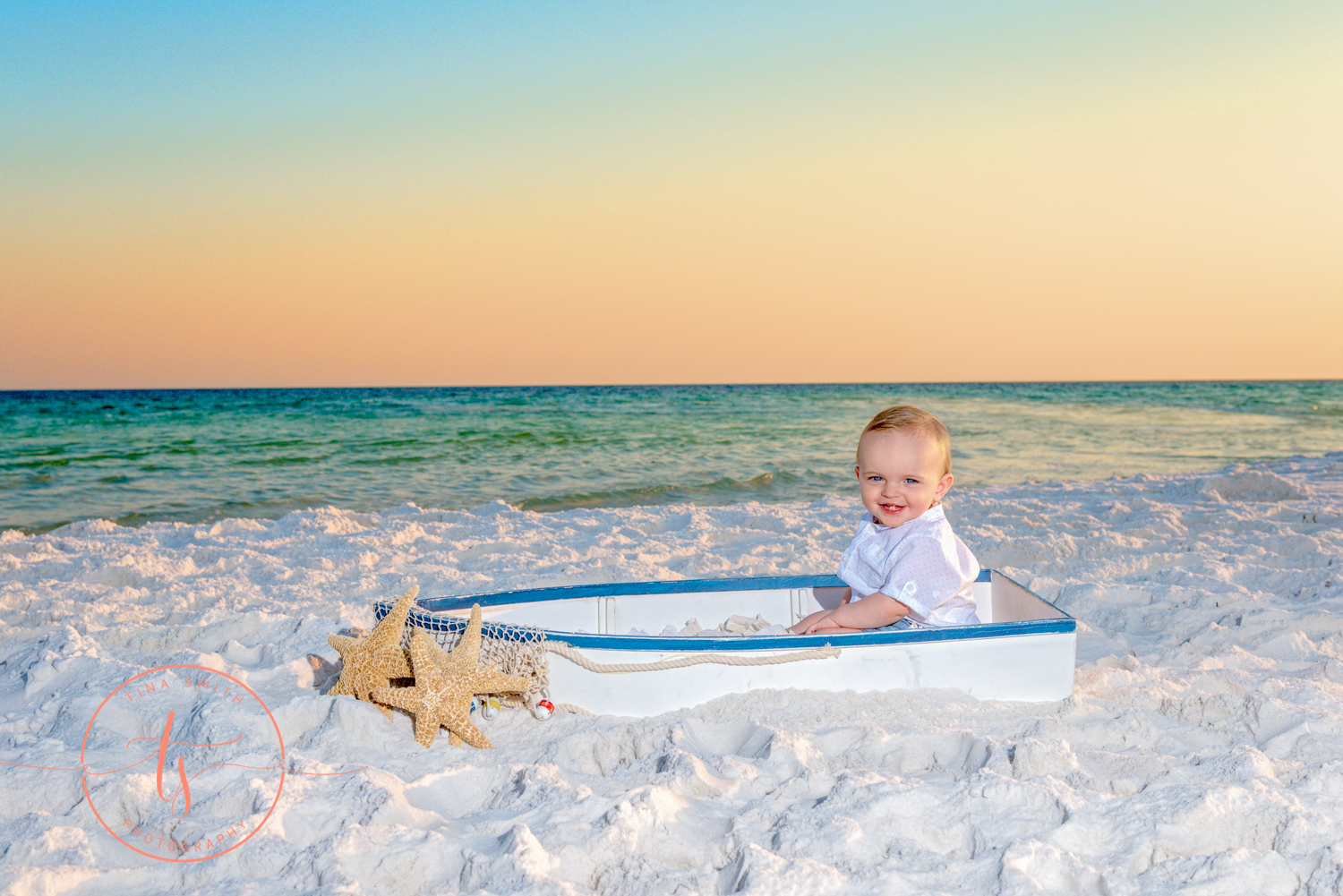 1 year boy sitting in a boat on beach smiling for photography
