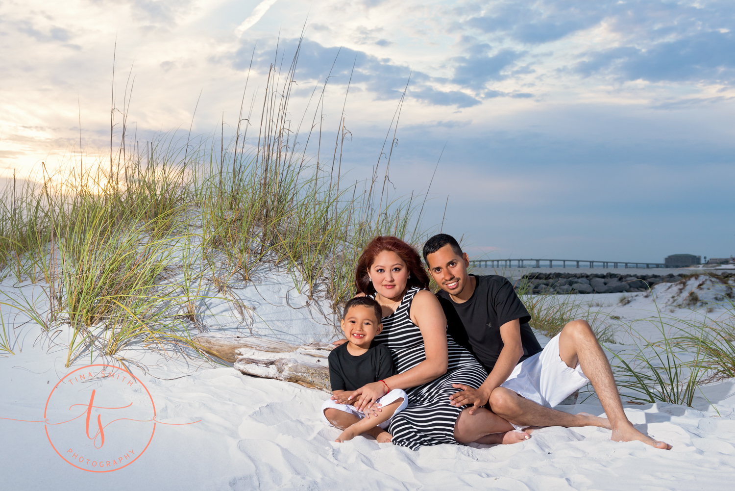 mom dad and son pose for maternity picture on beach in destin
