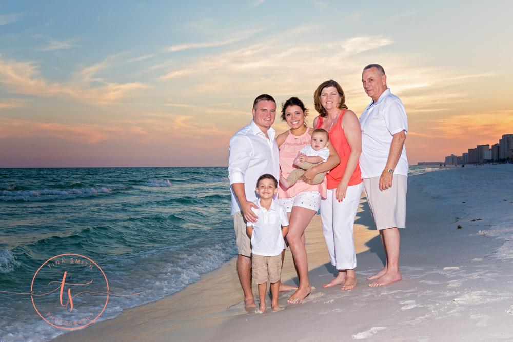 family on beach at sunset posing for destin photographer