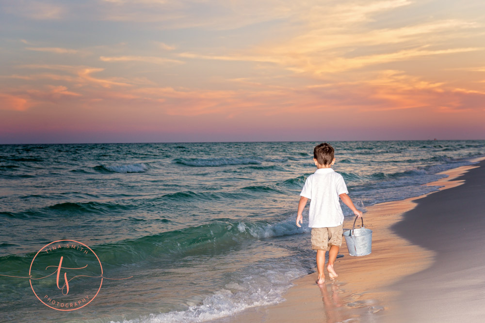 boy walking on beach in destin at sunset