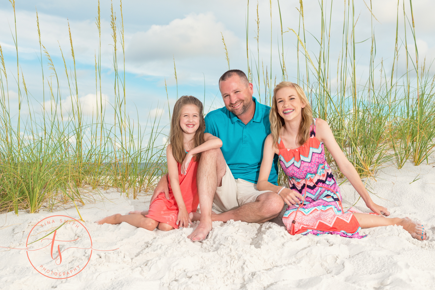 dad and daughters sitting on the beach smiling for destin photography