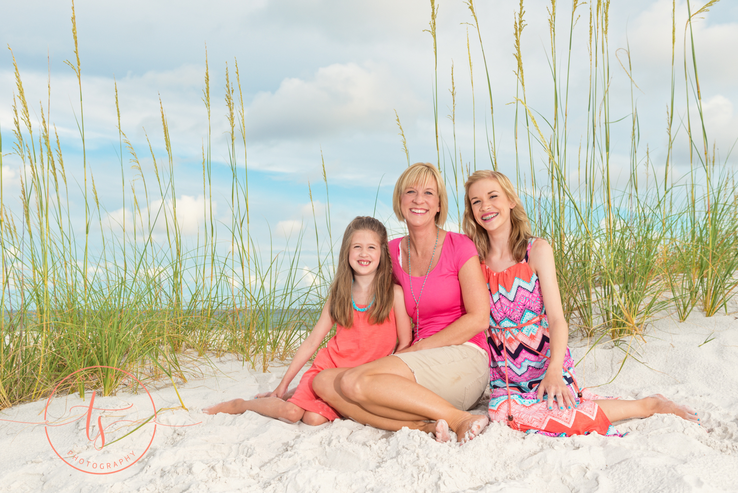 mom and daughters sitting on the beach posing for destin photographer