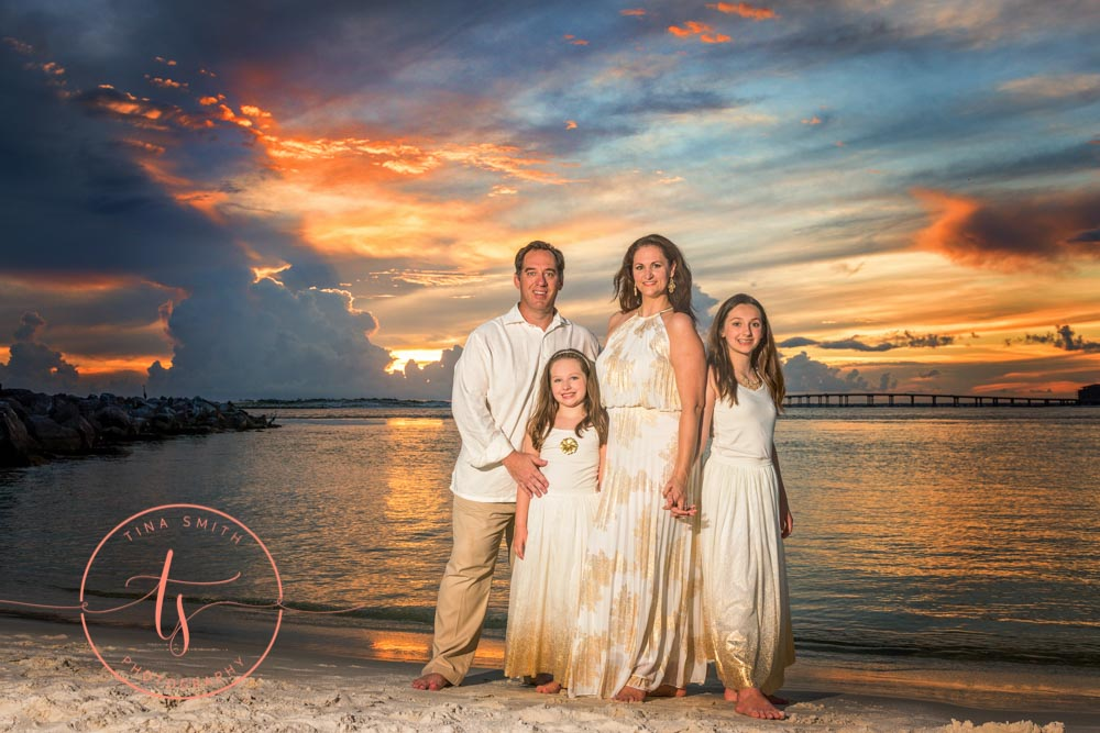 family dressed in formal wear standing on beach in destin at sunset