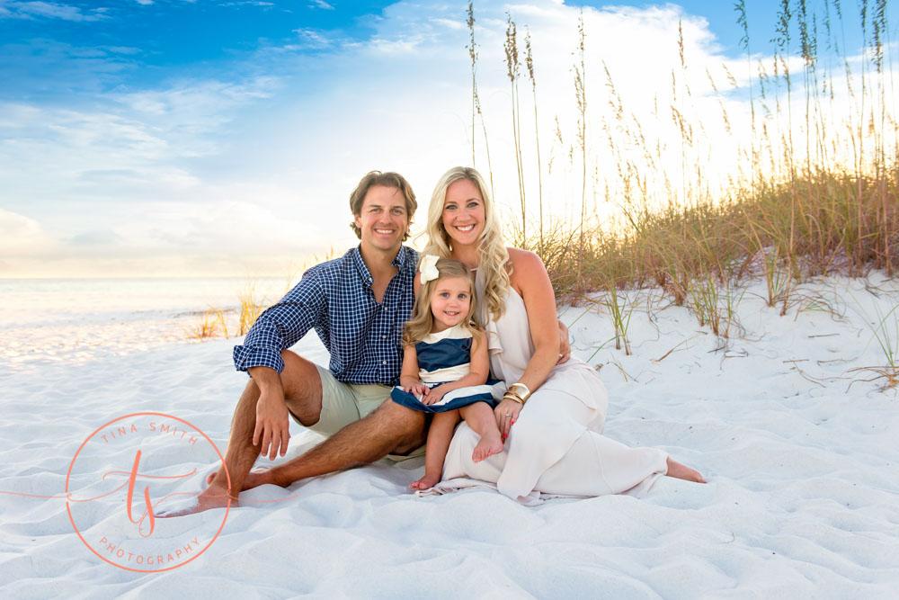 family of 3 sitting on the beach for destin family beach photographer