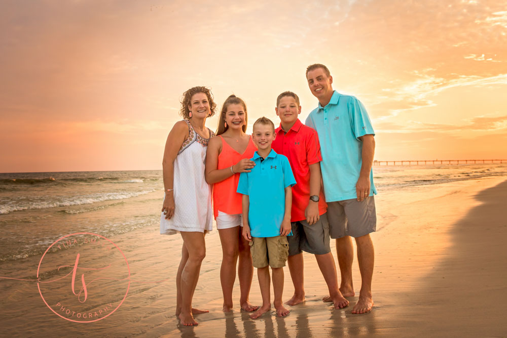 destin family beach photography posing at sunset in the waters edge