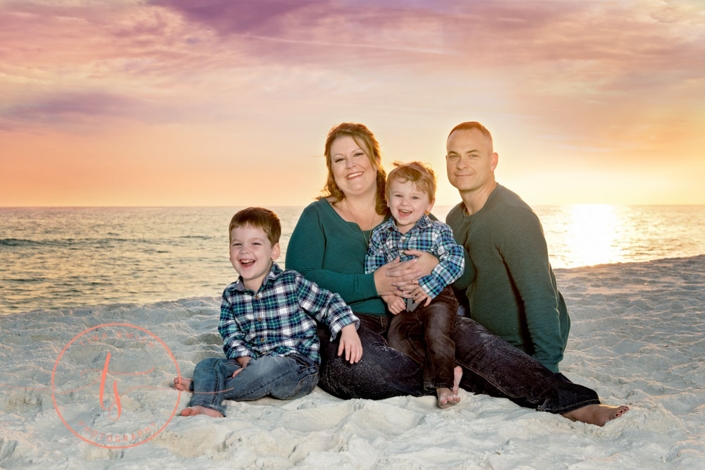 family sitting on the beach in destin smiling for photographer at sunset
