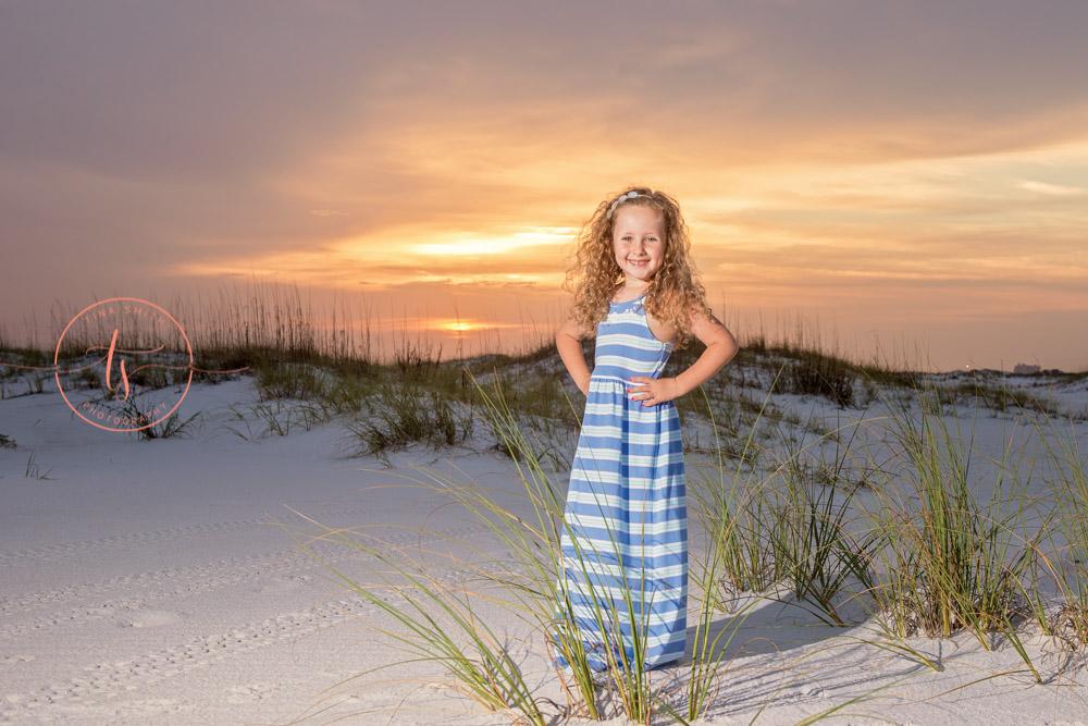 girl standing on beach at sunrise