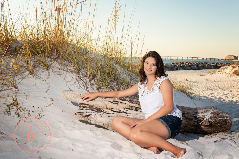 senior girl dressed in white leaning on driftwood on the beach in destin