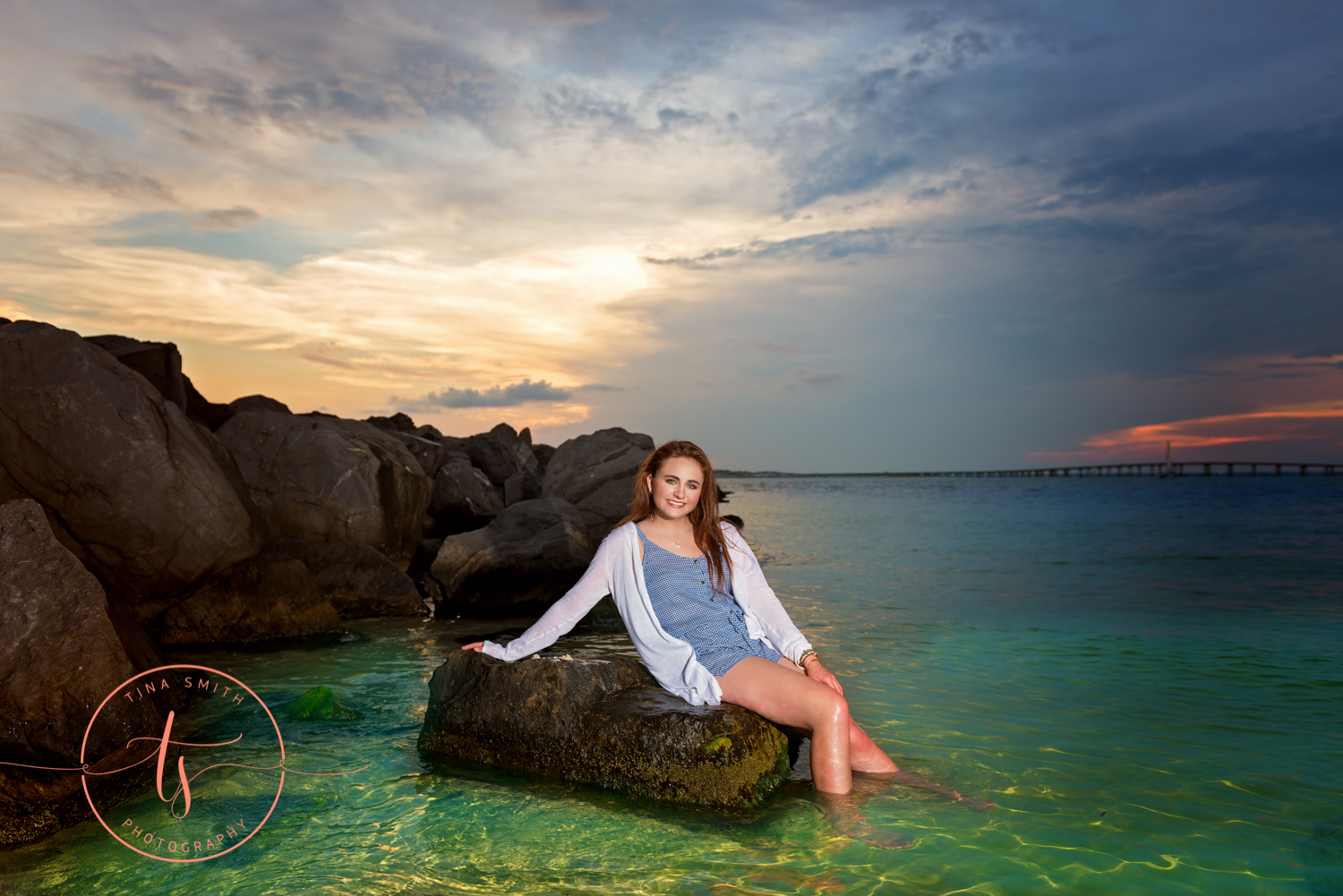 senior girl sitting on rock in emerald green water for photography