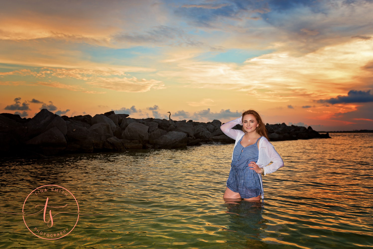 senior girl standing gin the ocean at sunset smiling for pictures