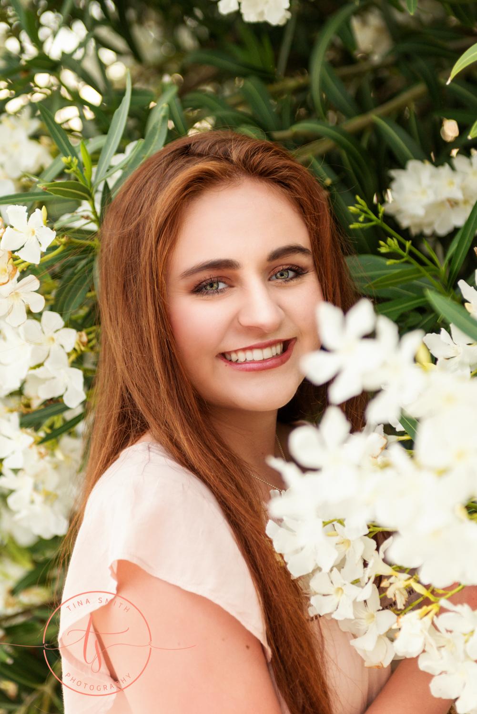 senior girl in front of white flowers on beach in destin