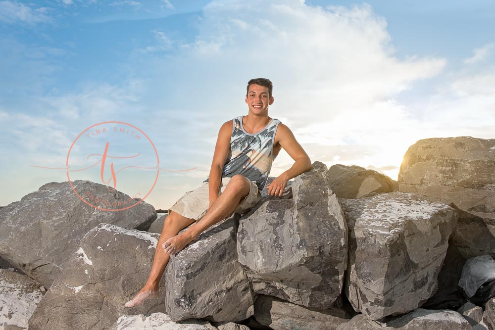 destin senior portraits photographer boy sitting on the jetties