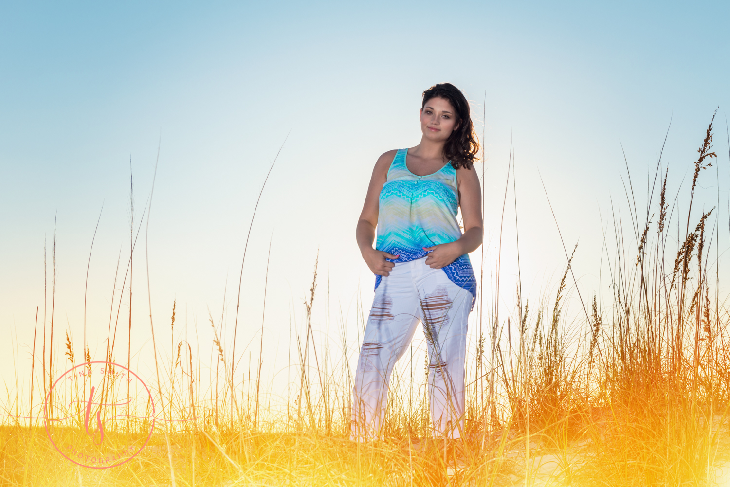 girl in white pants and teal shirt posing against sunset on dunes in destin