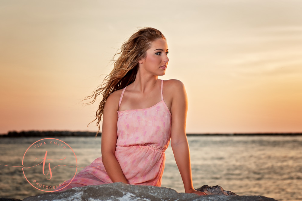 destin senior posing on a rock in the water