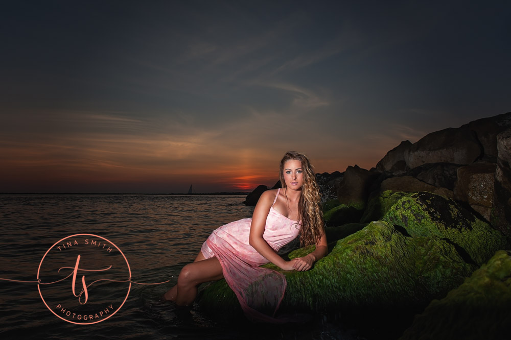 girl in pink dress lying in the water at sunset for destin senior portraits