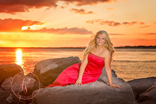 girl in pink formal gown laying on rocks at sunset on the beach for destin senior portrait photographer