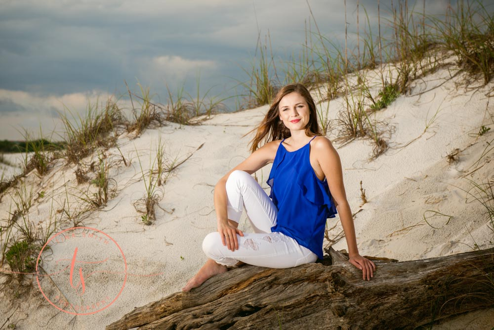 girl posing for destin senior portrait photography in a blue top and white capris sitting on drift wood