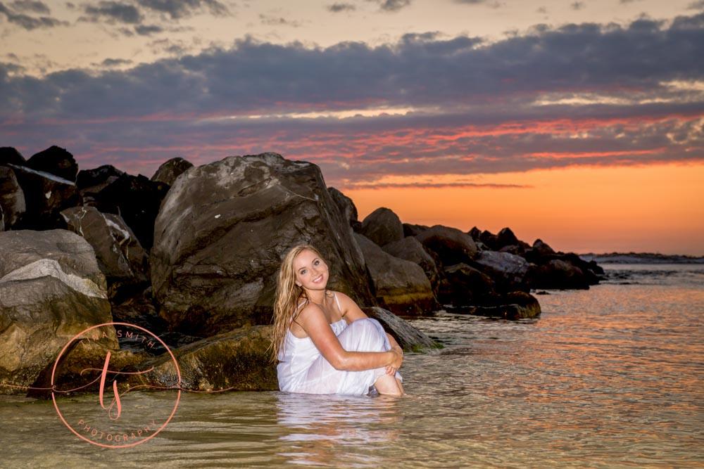 destin senior sitting in water at sunset in white dress posing for destin senior photographer