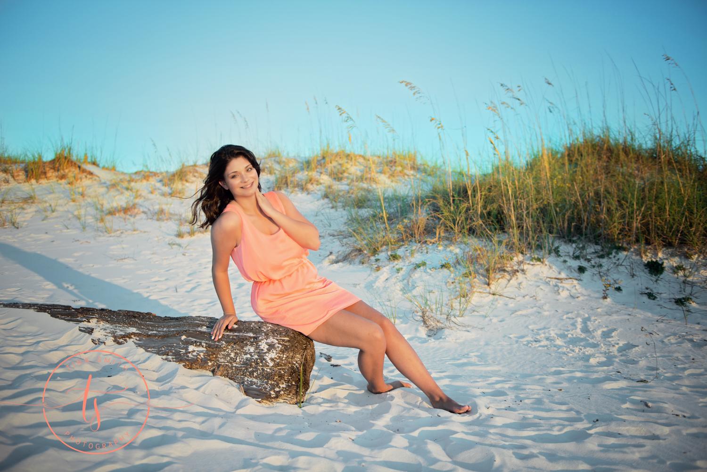 girl posing on log on beach in destin for senior portraits