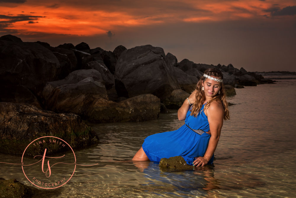 girl posing in water sitting on a rock in formal blue gown for destin senior portraits