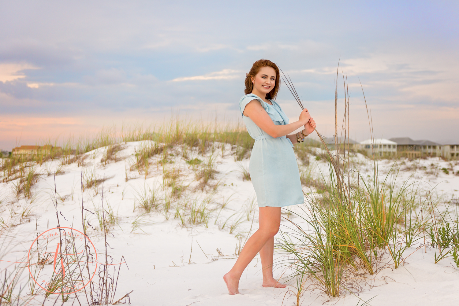 girl standing in a dress on the beach by sea oats for senior portraits in destin