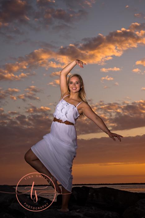senior girl doing a dance pose on rock on destin beach