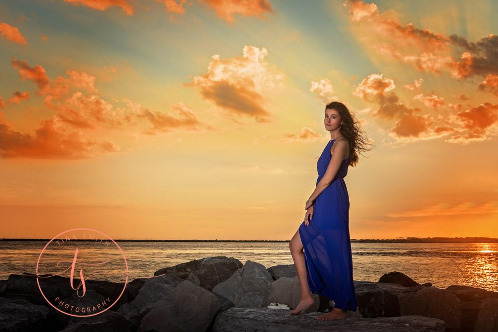 senior girl in blue dress posing on jetties at sunset in destin