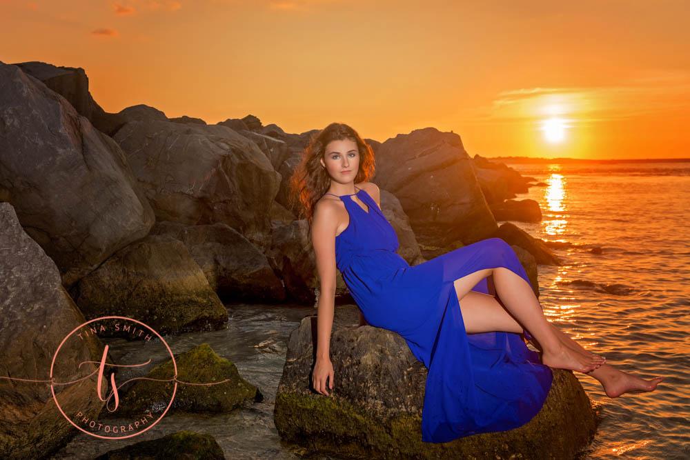 senior girl in blue dress posing on rock in water in destin