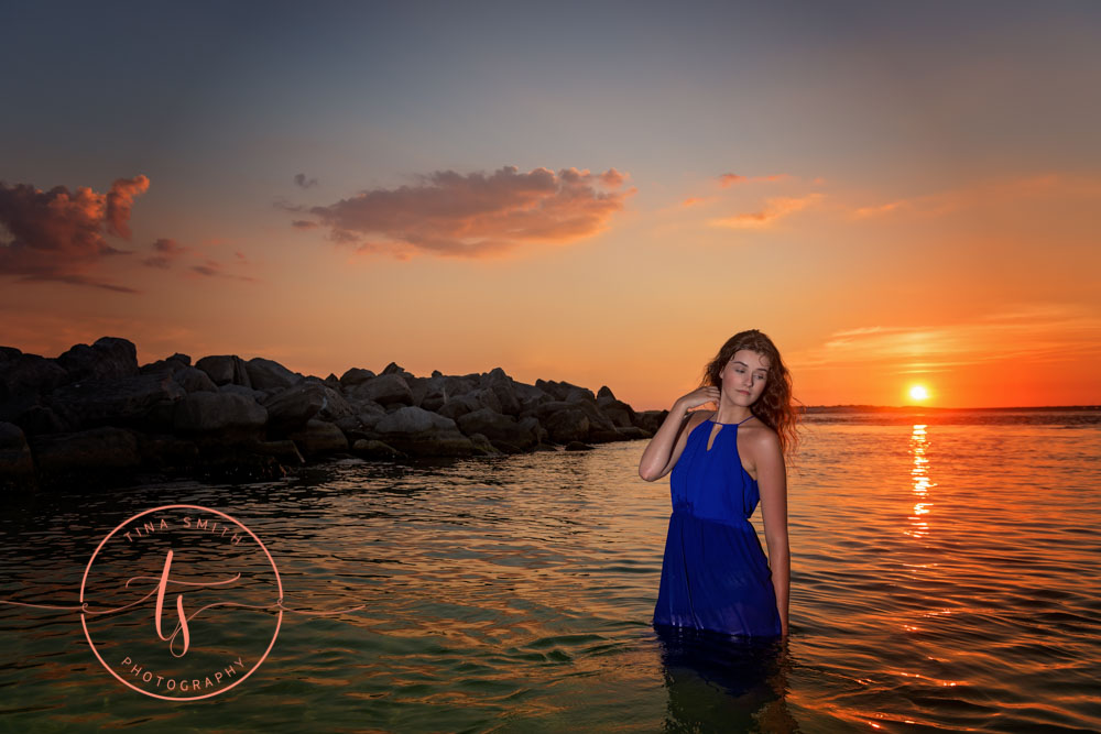 senior girl in blue dress posing in water at sunset in destin