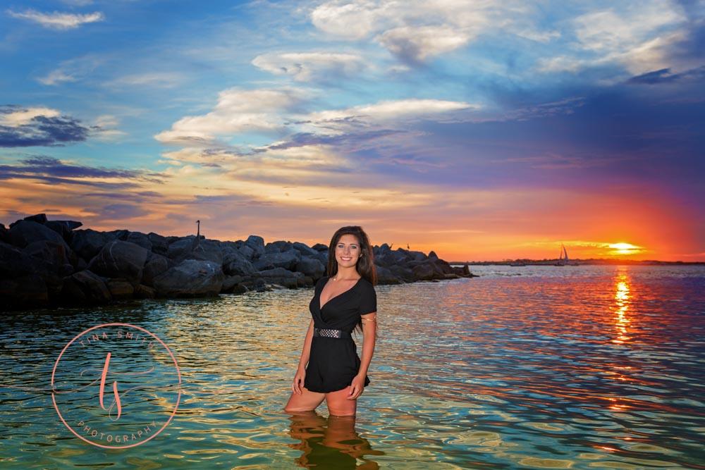 senior girl in black romper posing in water in destin