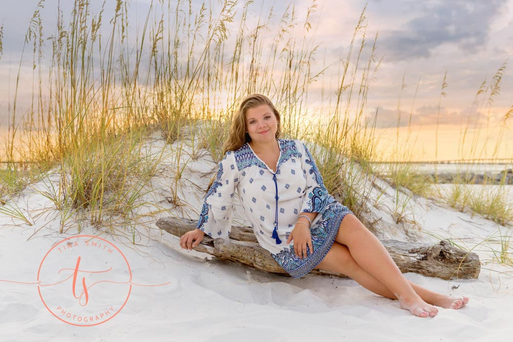 senior girl sitting on drift wood on beach in destin