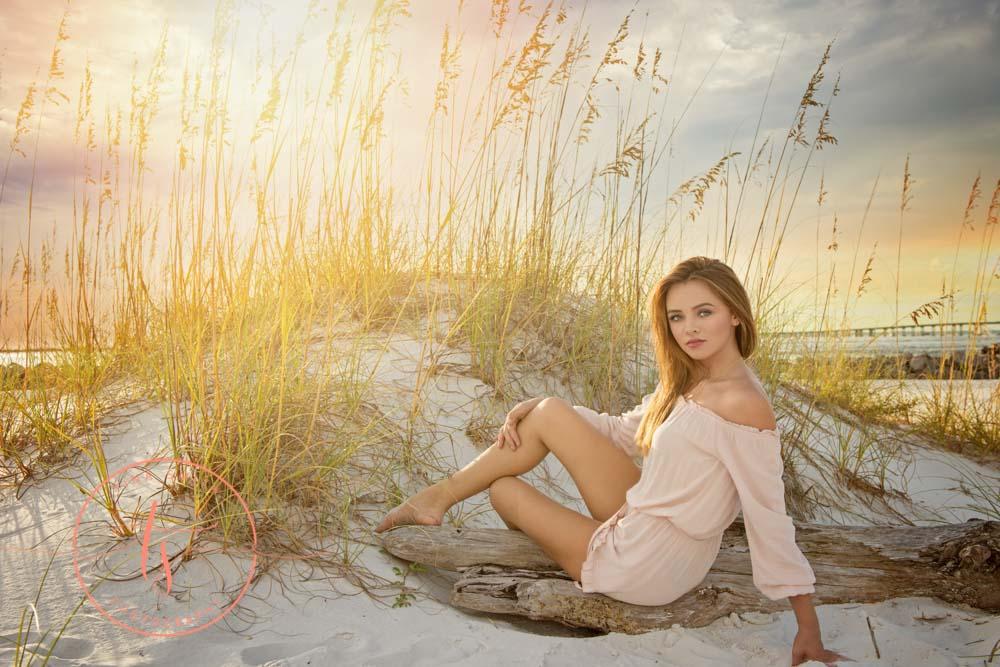 senior girl posing on drift wood on beach in destin