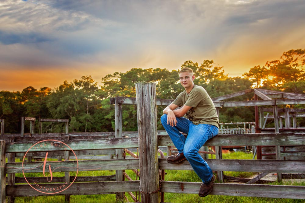 senior boy posing on a wooden fence