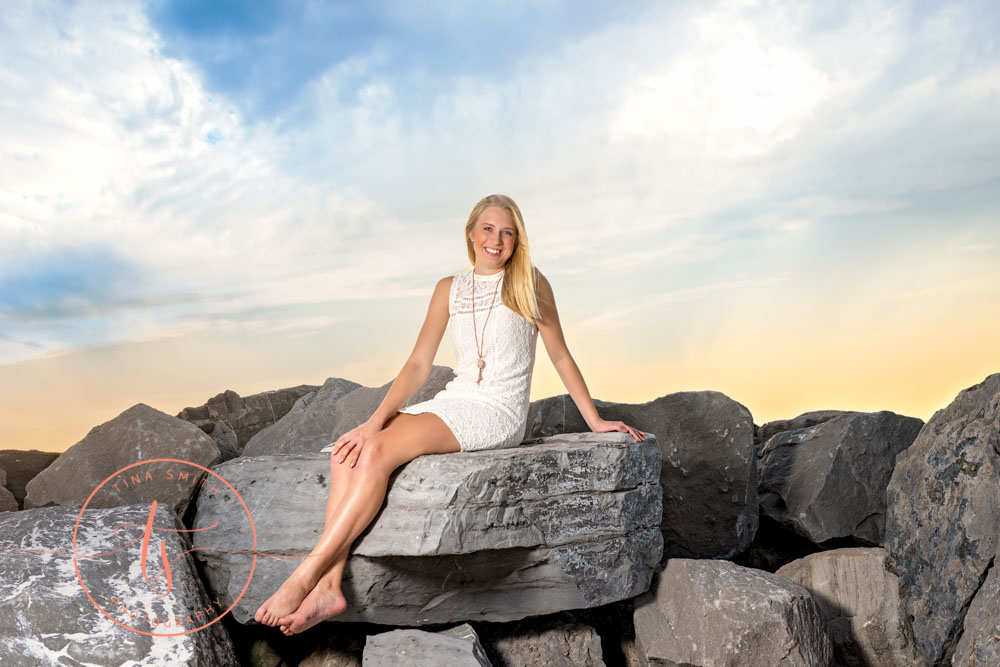 senior girl posing on jetties at sunset in destin