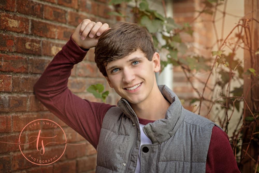 senior guy posing on brick wall ft walton beach high school