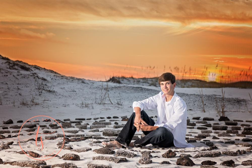 senior boy sitting in a ring of stones ft walton beach