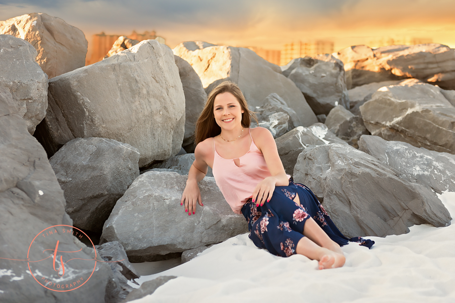 senior girl posing in front of rocks on the beach in destin