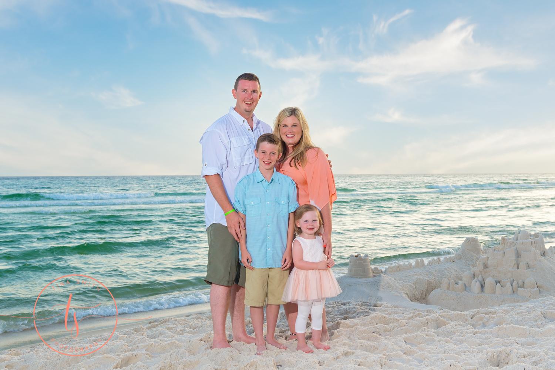 family of 4 posing on the seacrest beach