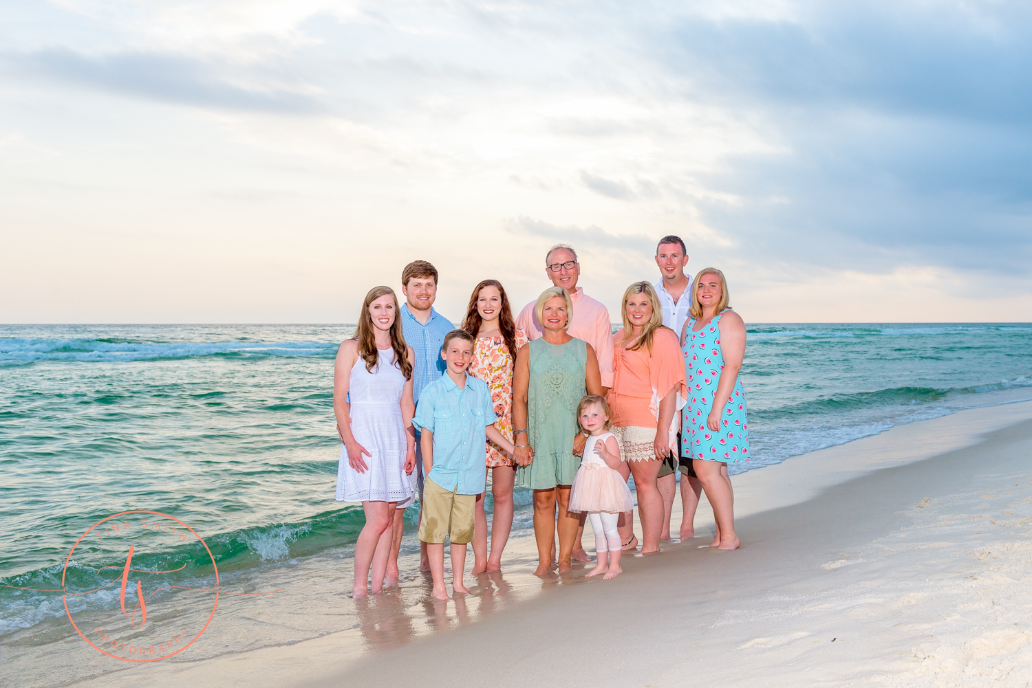 family standing in the water at seacrest beach for photography