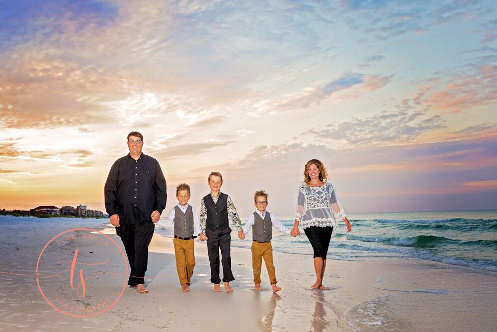 family walking down beach in destin at sunrise holding hands